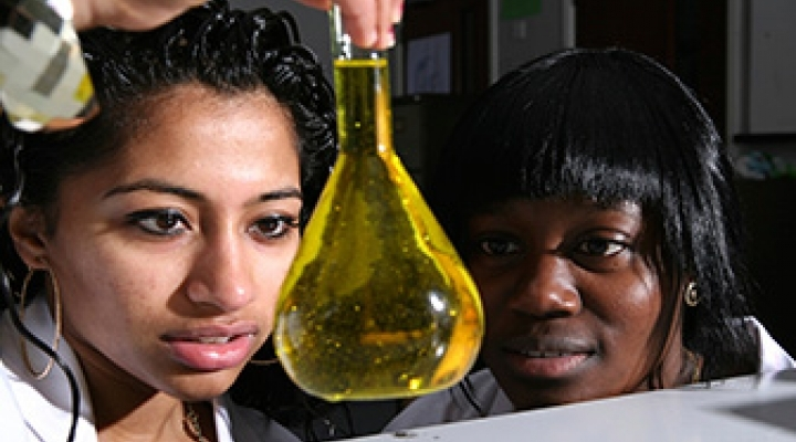 Two students looking at a flask of yellow liquid
